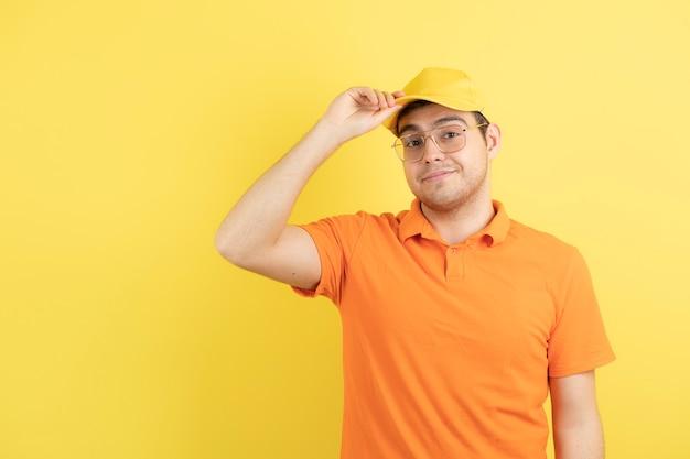 Jovem com uniforme laranja em pé e posando.