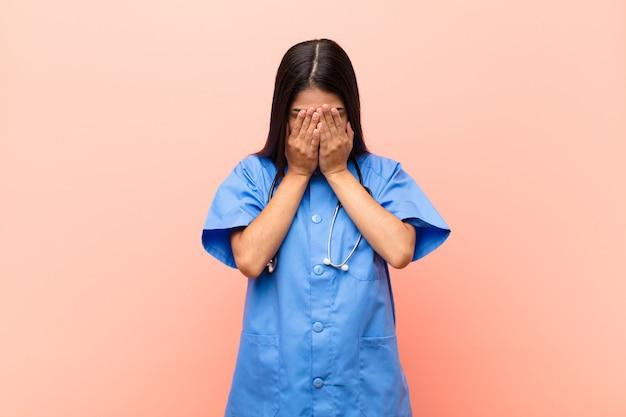 Jovem com uniforme médico e estetoscópio, cobrindo o rosto com as duas mãos enquanto chorava