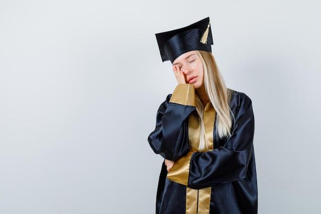 Jovem com vestido acadêmico segurando a mão na bochecha e parecendo cansada