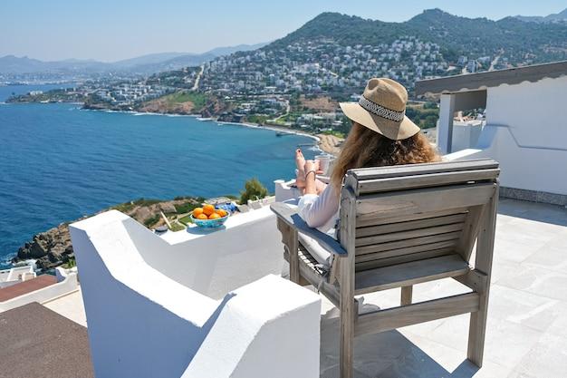 Jovem com vestido branco, chapéu de palha e xícara de café sentada no terraço branco