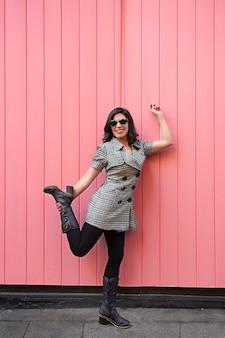 Jovem com vestido e óculos de sol fazendo poses de ioga na frente de uma parede rosa.