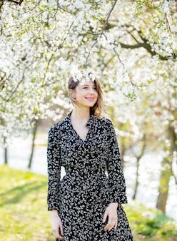 Jovem com vestido escuro fica perto de uma árvore florida no parque. temporada de primavera