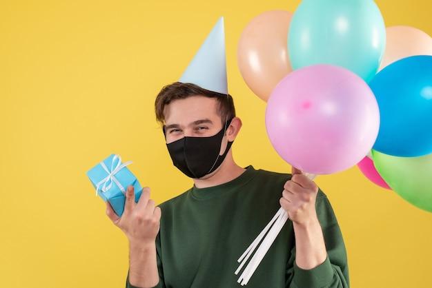 Jovem com vista frontal com boné de festa e máscara preta segurando uma caixa de presente azul e balões amarelos