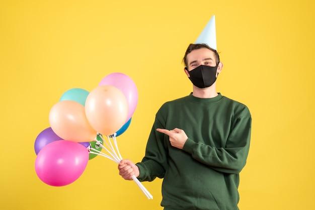 Jovem com vista frontal com tampa de festa apontando para balões coloridos em pé sobre fundo amarelo