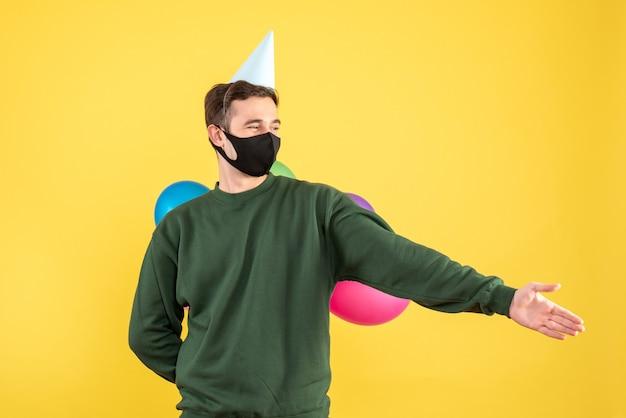 Jovem com vista frontal com tampa de festa e balões coloridos dando a mão em pé no amarelo
