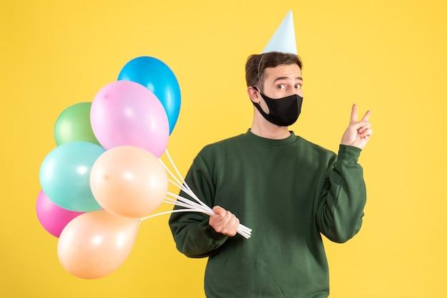 Jovem, com vista frontal, com tampa de festa e balões coloridos, fazendo o sinal da vitória em pé amarelo