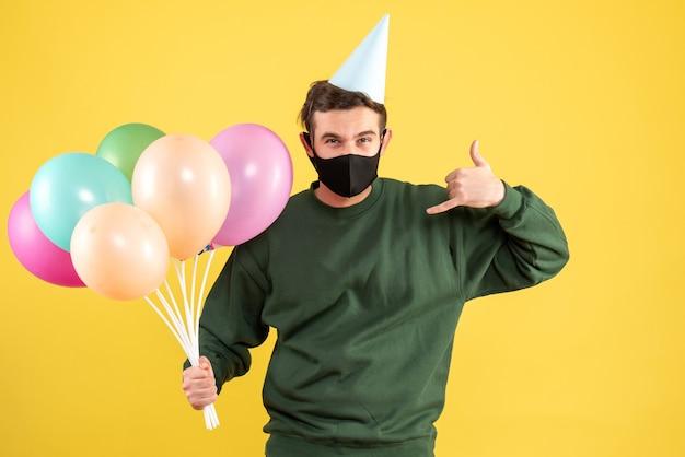 Jovem com vista frontal com tampa de festa e balões coloridos fazendo sinal de me chame de pé no amarelo