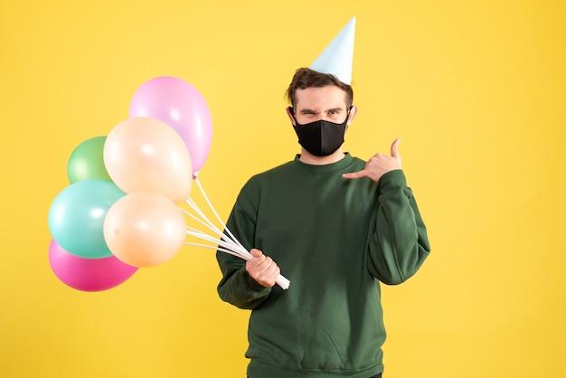 Jovem com vista frontal com tampa de festa e balões coloridos fazendo sinal de telefone em amarelo