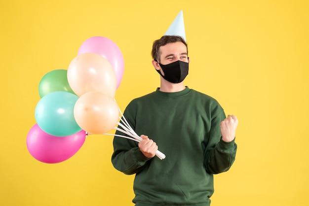 Jovem com vista frontal com tampa de festa e balões coloridos mostrando o gesto vencedor em amarelo