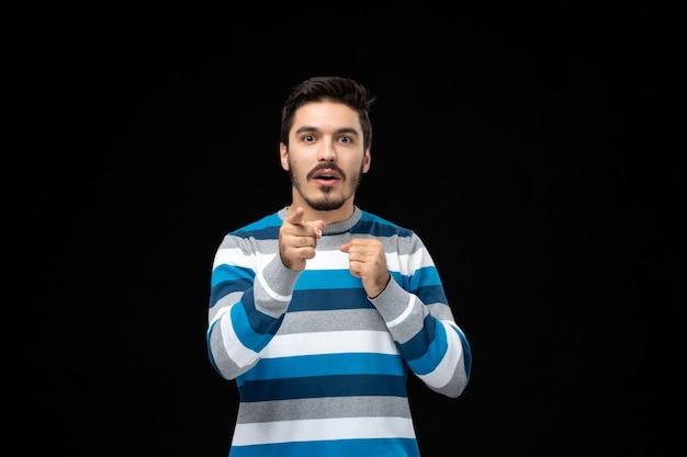 Jovem com vista frontal de camisa listrada azul apontando para você