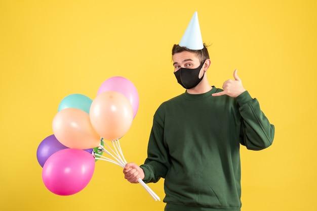 Jovem com vista frontal e boné de festa e balões coloridos fazendo sinal de me ligar amarelo