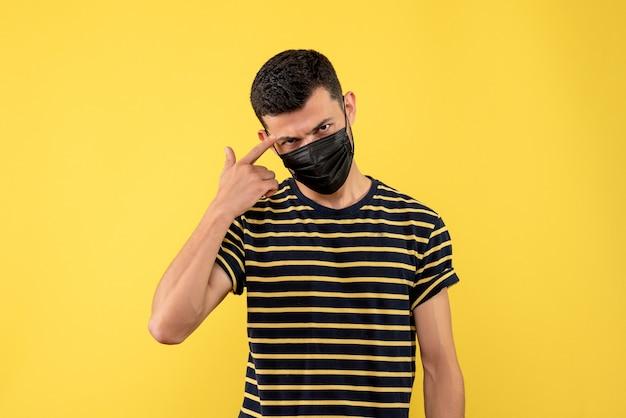 Jovem com vista frontal em uma camiseta listrada em preto e branco com fundo amarelo