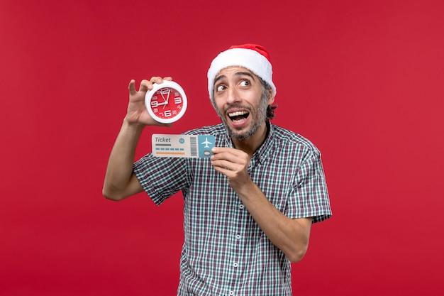 Jovem com vista frontal segurando o bilhete e o relógio na parede vermelha, tempo de emoção masculina vermelha
