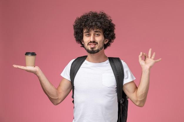 Jovem, com vista frontal, segurando um copo de café de papel na mão e mostrando um gesto de ok