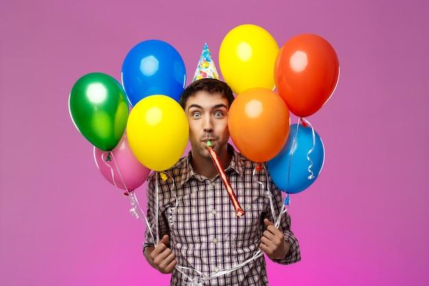 Jovem comemorando aniversário, segurando balões coloridos sobre parede roxa.