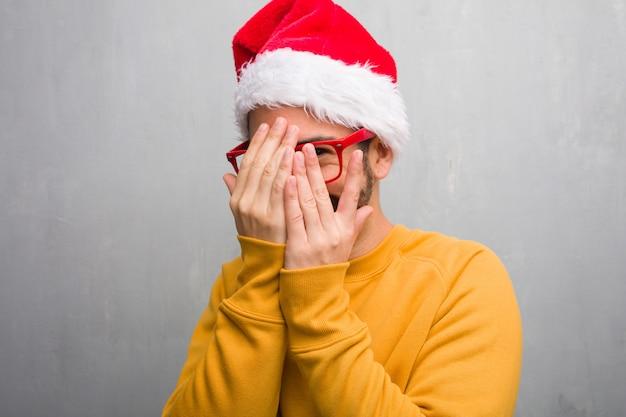 Jovem comemorando o dia de natal segurando presentes envergonhados e rindo ao mesmo tempo