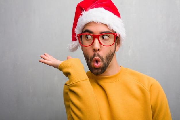 Jovem comemorando o dia de natal segurando presentes segurando algo com a mão