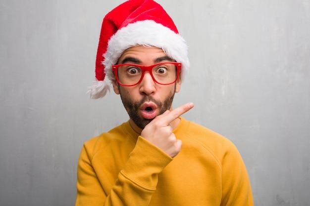 Jovem comemorando o dia de natal segurando presentes sorrindo e apontando para o lado