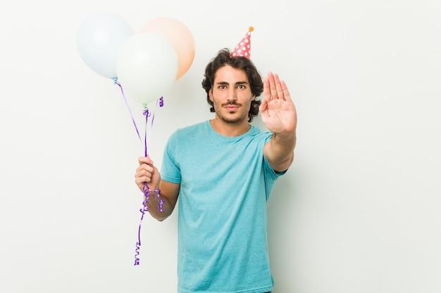 Jovem comemorando uma festa segurando balões em pé com a mão estendida, mostrando o sinal de stop, impedindo-o.