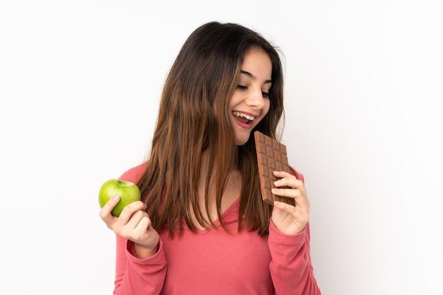Jovem comendo chocolate e maçã sobre parede isolada