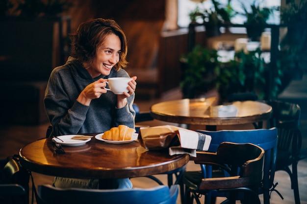 Jovem comendo croissants em um café