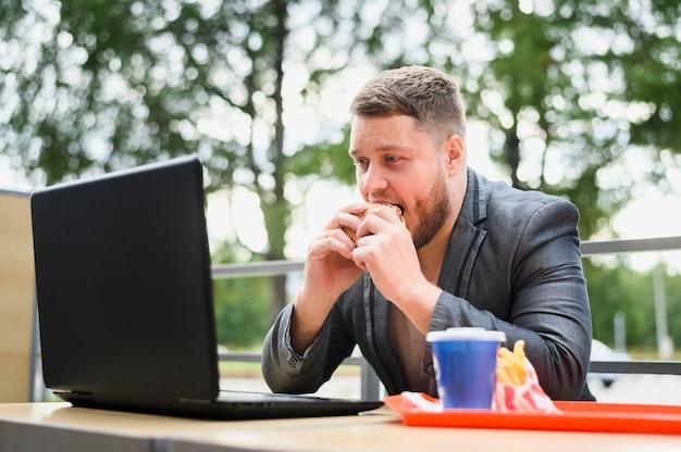 Jovem comendo enquanto olha para o laptop