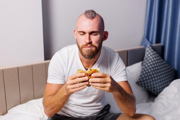 Jovem comendo fast food em casa no quarto na cama