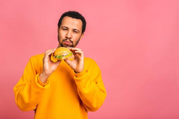 Jovem comendo hambúrguer isolado sobre rosa