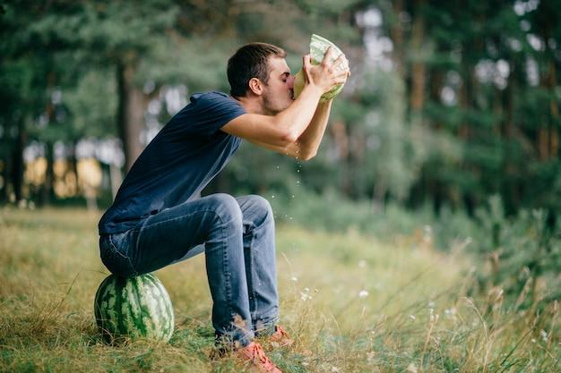 Jovem comendo melancia e bebendo seu suco na natureza.