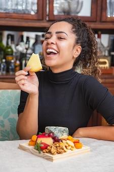 Jovem comendo queijo. mulher comendo salgadinhos de queijo