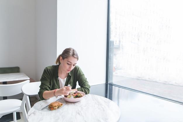 Jovem comendo salada na mesa na janela no restaurante com luz interior.