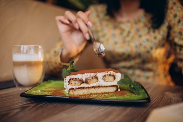 Jovem comendo um delicioso tiramisu em um café