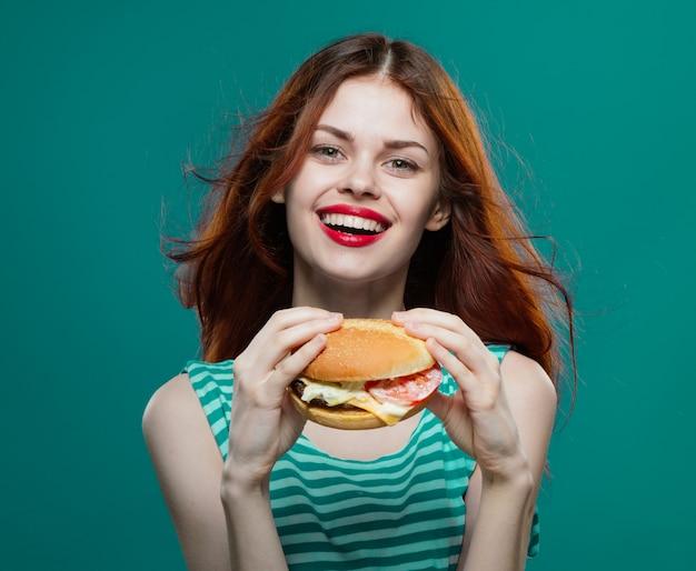 Jovem comendo um hambúrguer suculento, hambúrguer delicioso fast-food
