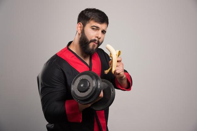 Jovem comendo uma banana e segurando um haltere.