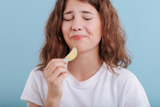 Jovem comendo uma fatia de limão