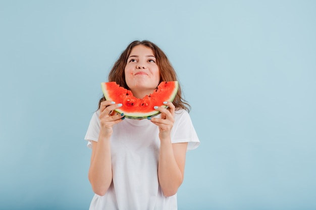 Jovem comendo uma fatia de melancia