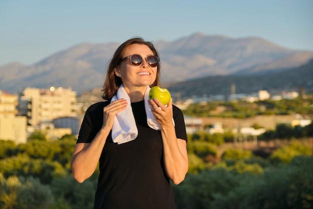 Jovem comendo uma maçã ao ar livre