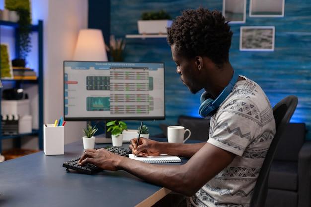 Jovem comerciante afro-americano escrevendo gráfico de ganhos criptográficos em um caderno