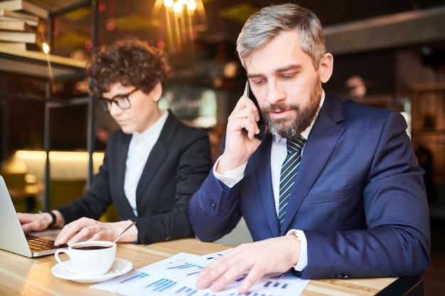Jovem comerciante em trajes formais, consultando um dos clientes no telefone enquanto analisa gráficos financeiros no café