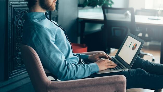 Jovem comerciante focado em homem sem rosto trabalhando em um laptop