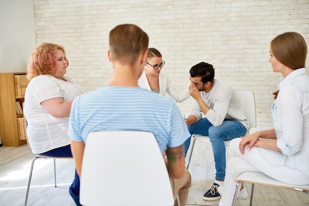 Jovem compartilhando problemas na sessão de terapia de grupo