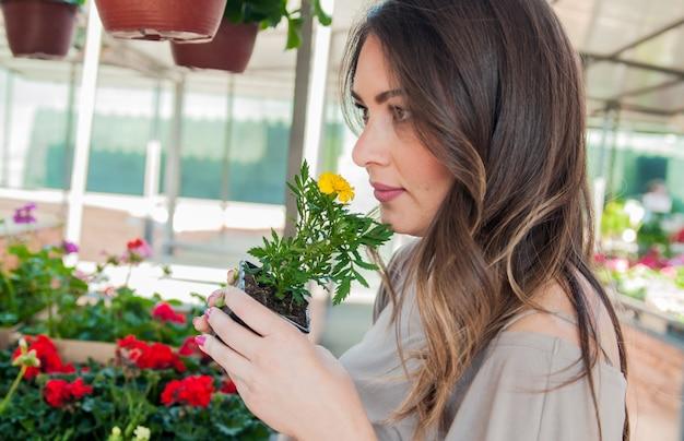 Jovem comprando flores em um centro de jardim. minhas flores favoritas. mulher olhando flores em uma loja. retrato de uma mulher sorridente com flores em viveiro de plantas