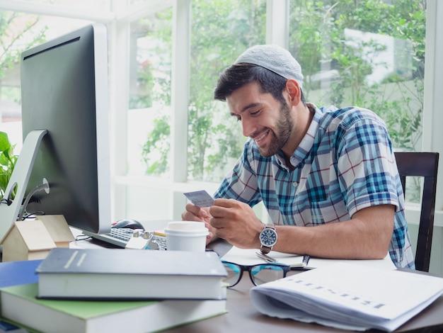 Jovem, compras on-line com cartão de crédito em casa