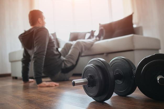 Jovem comum praticando esportes em casa. corte a visão de um iniciante ou calouro na atividade de treino em seu apartamento.