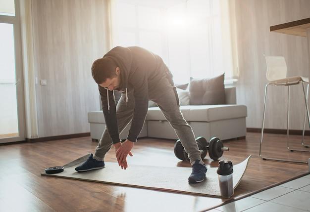 Jovem comum praticando esportes em casa. indivíduo do sexo masculino adulto, estendendo-se até os pés com as mãos.