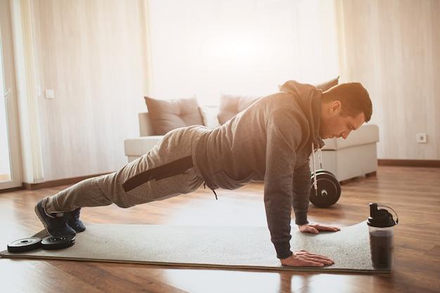 Jovem comum praticando esportes em casa. posição da prancha nos punhos ou fazendo flexões.