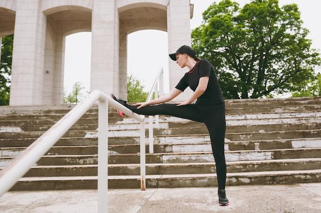 Jovem concentrada, atlética, linda morena, de uniforme preto e boné, fazendo exercícios de alongamento esportivo, aquecimento antes de correr no parque da cidade ao ar livre