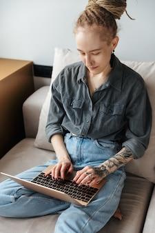 Jovem concentrada com dreadlocks e piercings dentro de casa usando o computador portátil.