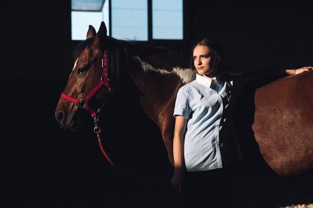 Jovem concentrada em pé ao ar livre perto de seu cavalo