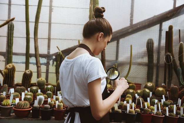 Jovem concentrada em pé na estufa perto de plantas